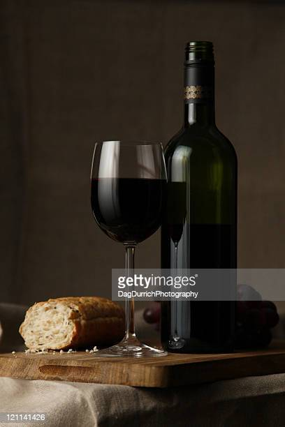 Red wine and peace of bread on table