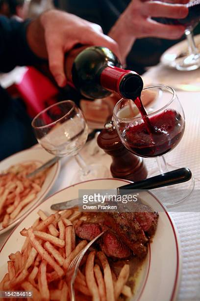 Red wine being poured to accompany steak frites