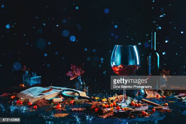 Red wine bottle and tall glass in dark autumn still life with rain drops, books, fallen leaves and berries. Conceptual food photography. Black background with splashes.