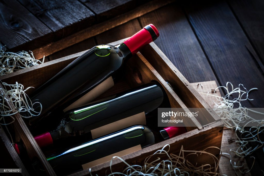 Red wine bottles packed in a wooden box shot rustic wooden table : Stock Photo