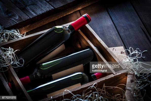 Red wine bottles packed in a wooden box shot rustic wooden table
