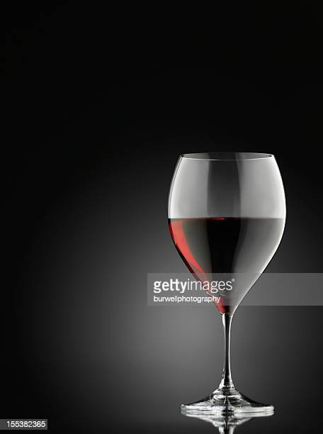 Red wine glass against a black background