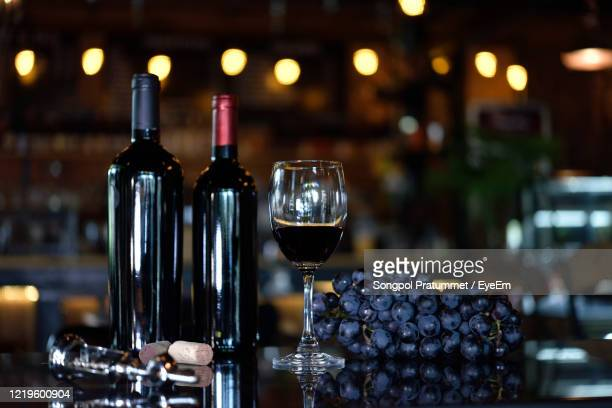 red wine glass on the floor with a bottle of red wine and two bottles of red wine were put aside. - ワイナリー ストックフォトと画像