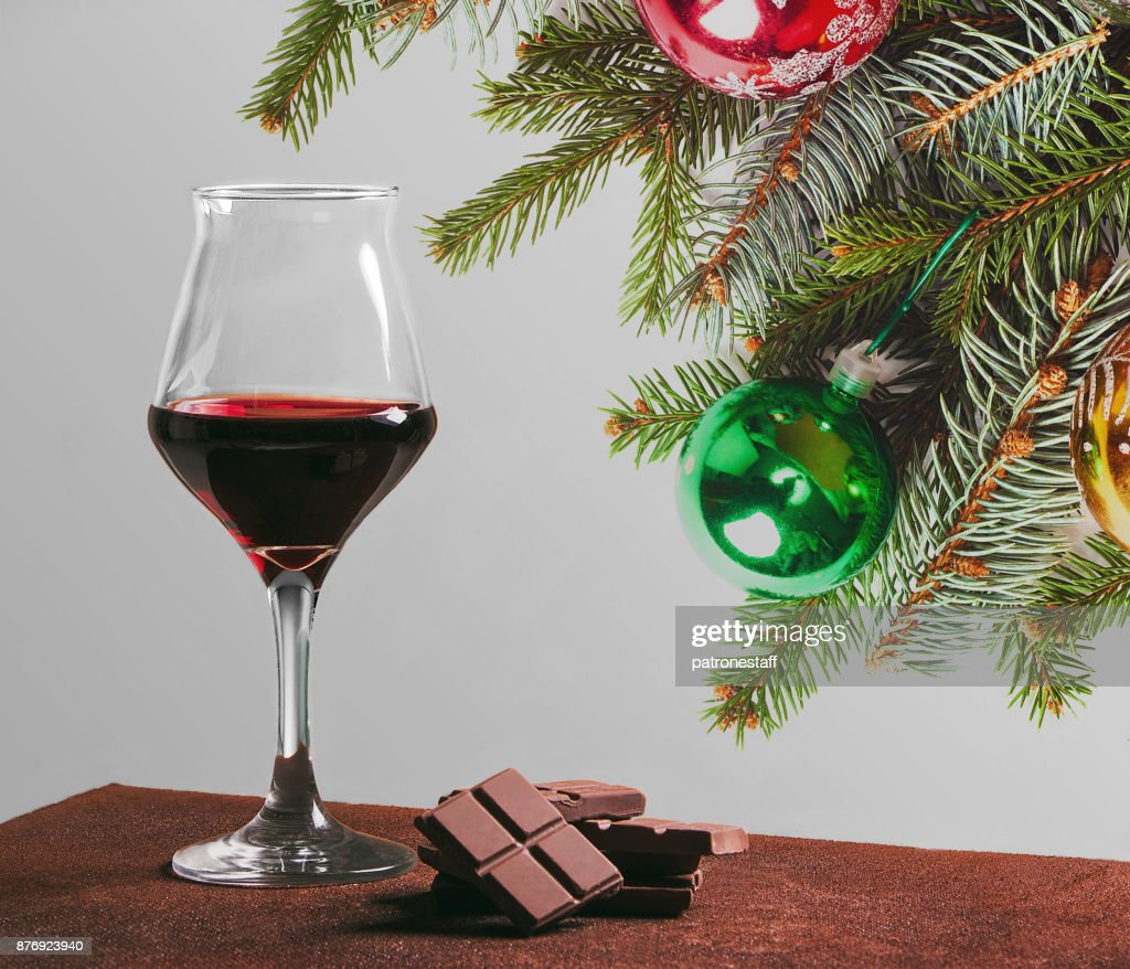 red wine glass with chocolate and christmas decorations stock photo