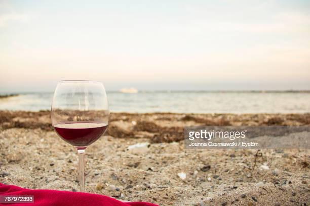 Red Wine In Wineglass At Beach During Sunset