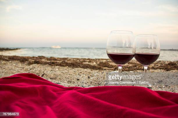 red wine in wineglasses at beach during sunset - picnic blanket stock pictures, royalty-free photos & images