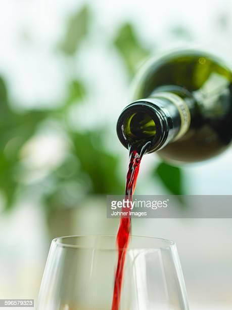red wine pouring into wine glass - västra götalands län stockfoto's en -beelden