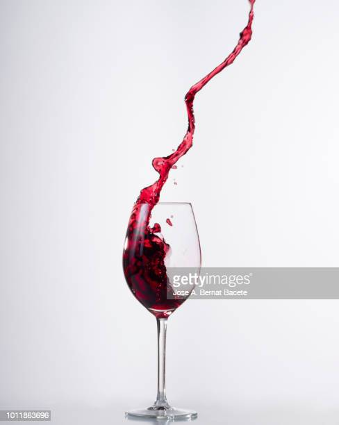 red wine splashing in glass in front of white background. - copa de vino fotografías e imágenes de stock