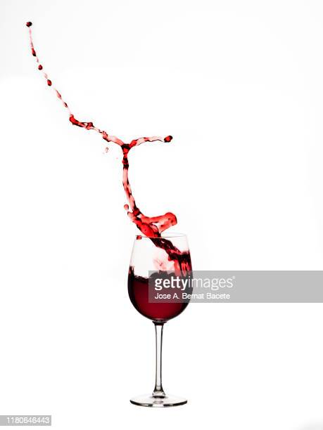 red wine splashing in glass in front of white background - drinking glass stock pictures, royalty-free photos & images