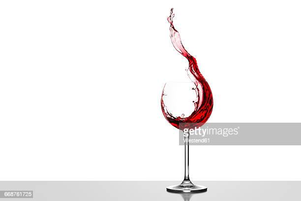 Red wine splashing in glass in front of white background