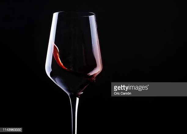 red wine swirling into glass - red wine stock pictures, royalty-free photos & images