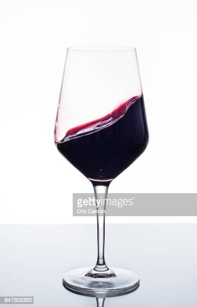red wine swirling into glass - copa de vino fotografías e imágenes de stock