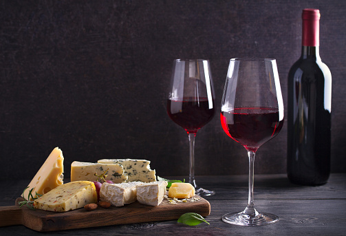 Red wine with cheese on chopping board. Wine and food concept 1154364625