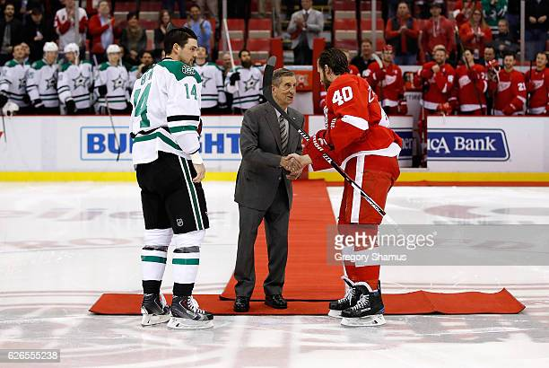 Red Wing Hall of Famer Ted Lindsay does a ceremonial puck drop between Jamie Benn of the Dallas Stars and Henrik Zetterberg of the Detroit Red Wings...