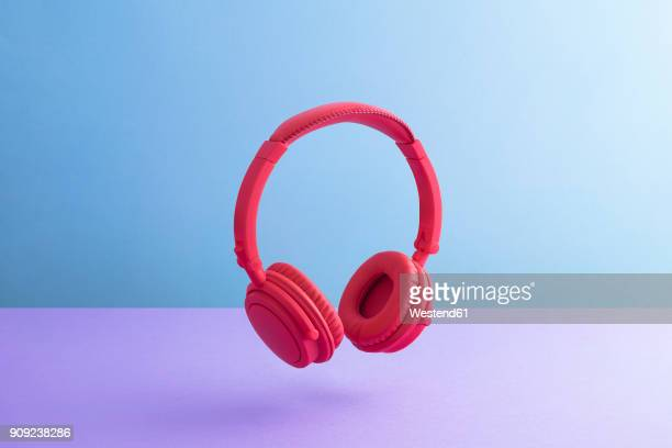 red wireless headphones - purple background stock photos and pictures