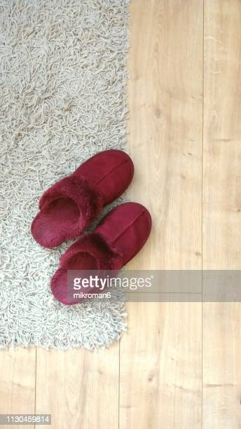 red woman's slipper on wooden floor and rug - スリッパ ストックフォトと画像
