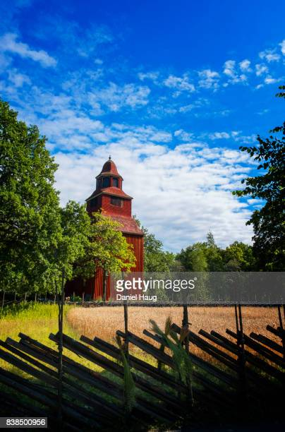Red Wooden Church in Rural Sweden Sits Amongst Wheat Field and Trees