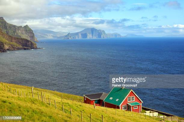 a red wooden house on an grassy island at the edge of the water - rainer grosskopf stock pictures, royalty-free photos & images