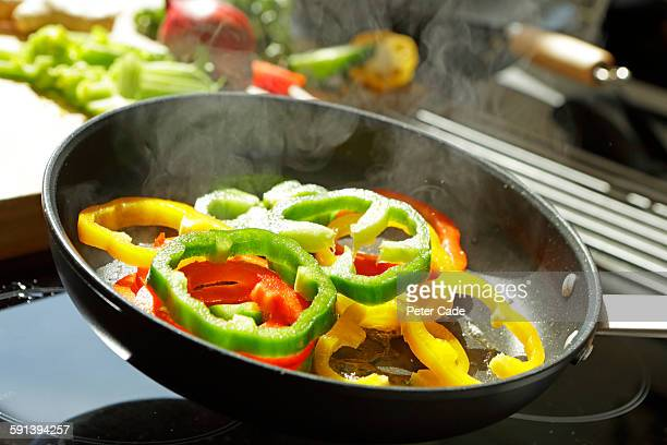 Red, yellow and green peppers frying in pan