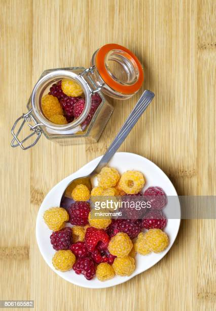 Red, yellow, and orange raspberries Fruits In Bowl and jar