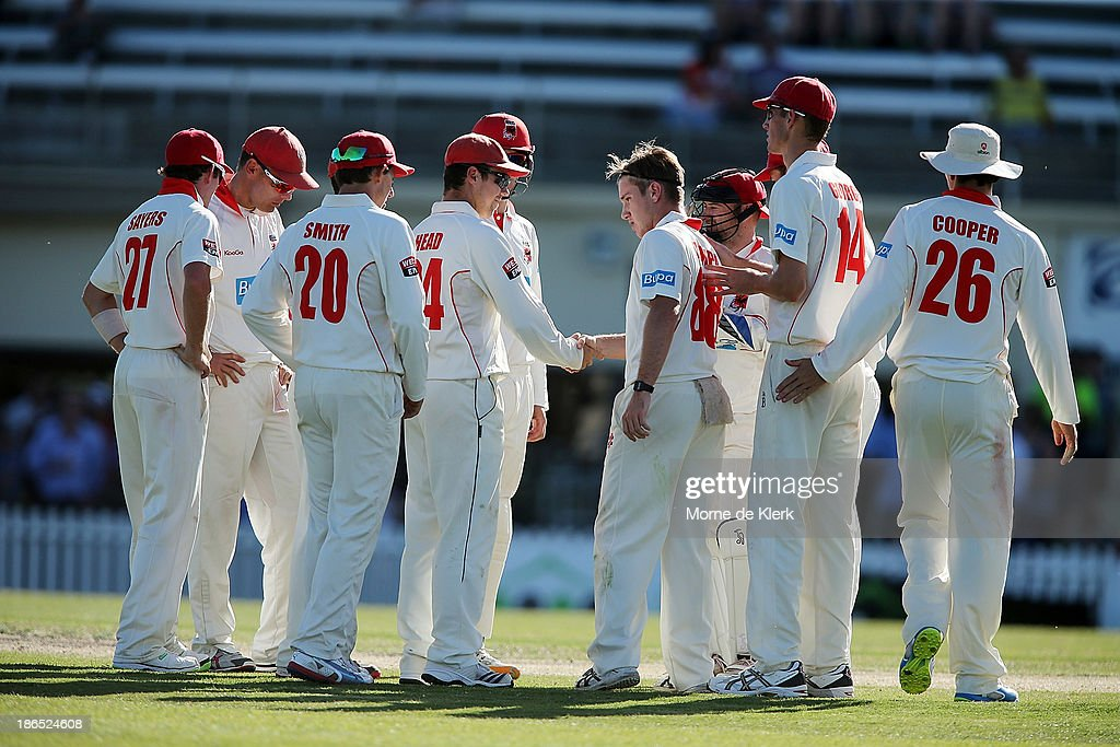 Redbacks players celebrate with Adam Zampa after his first wicket during day three of the Sheffield Shield match between the South Australia Redbacks and the Queensland Bulls at Glenelg Oval on November 1, 2013 in Adelaide, Australia.