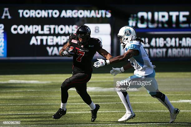 TORONTO ON AUGUST 23 RedBlacks Maurice Price is chased by Argos Akwasi OwusiAnsah during the 1st half of CFL action as the Toronto Argonauts take on...