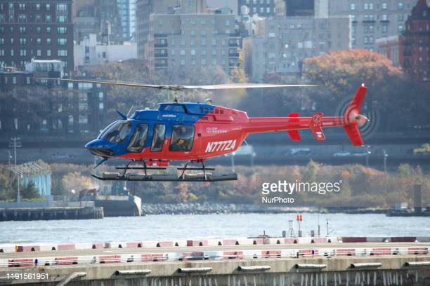 A redblue helicopter Bell 407GXP with registration N777ZA of Zip Aviation full of passengers as seen landing at helipad of New York Port Authority...