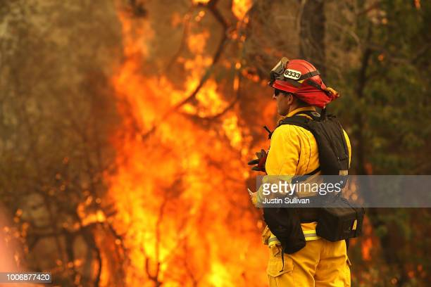 Redding firefighter looks on as the Carr Fire moves through the area on July 28 2018 in Redding California A Redding firefighter and a bulldozer...