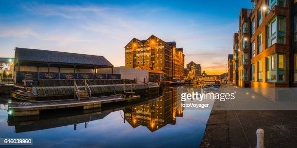 Redeveloped dockland warehouses barges waterfront apartments panorama at sunset