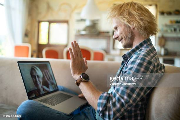 redhair man sitting on sofa video calling remote friend - employee engagement stock pictures, royalty-free photos & images