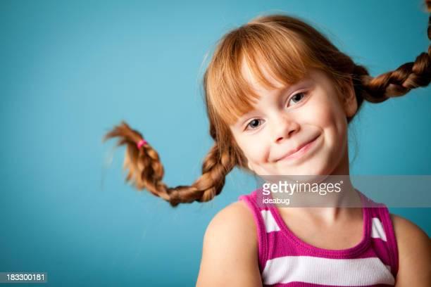 Red männlichen Mädchen mit nach oben, geflochtener Zopf, einem Lächeln und Hautunebenheiten