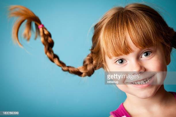 Red männlichen Mädchen mit nach oben, geflochtener Zopf und einem Lächeln