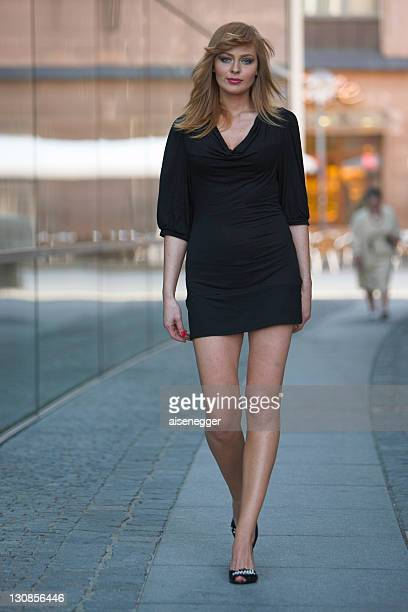 Red-haired leggy model in front of a glass facade in Nuremberg, Bavaria, Germany