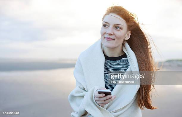 red-haired woman holding smart phone on beach - hope stock pictures, royalty-free photos & images