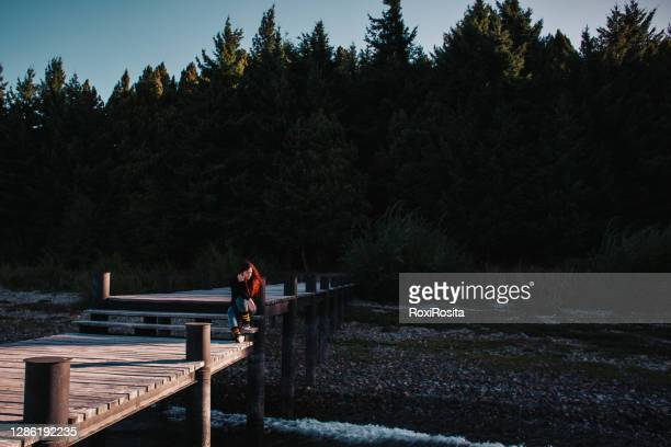 redhaired woman sitting on a pier with her back to the forest - bariloche stock pictures, royalty-free photos & images