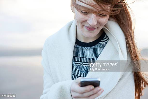 red-haired woman texting on beach - leanincollection stock pictures, royalty-free photos & images