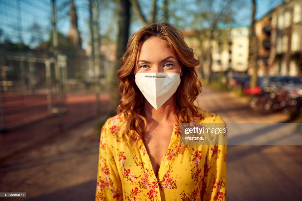 Red-haired woman wearing a FFP2 face mask in the city : Stockfoto