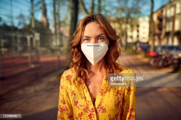 red-haired woman wearing a ffp2 face mask in the city - schutzmaske stock-fotos und bilder