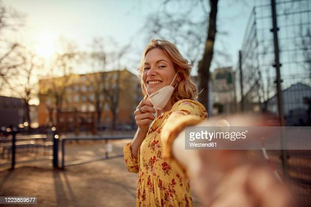 red-haired woman wearing a ffp2 face mask in the city - clumsy stockfoto's en -beelden