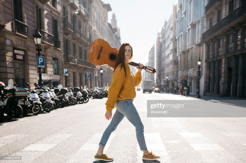 Red-haired woman with a guitar on zebra crossing : Stock Photo
