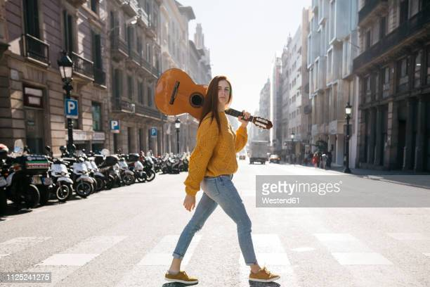 red-haired woman with a guitar on zebra crossing - musician stock pictures, royalty-free photos & images