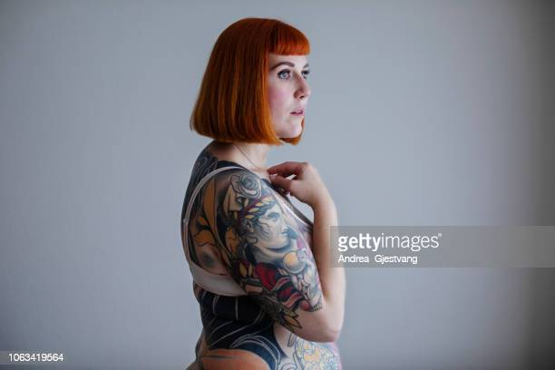 Red-haired woman with full body tattoos