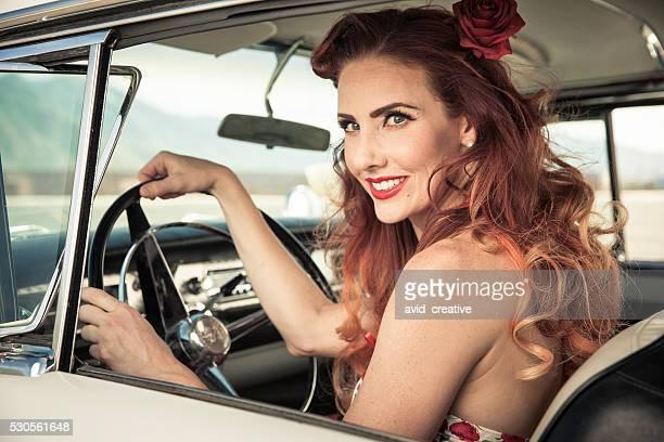 Rotes Haar 50er Pin-up Mädchen mit dem Klassiker Auto