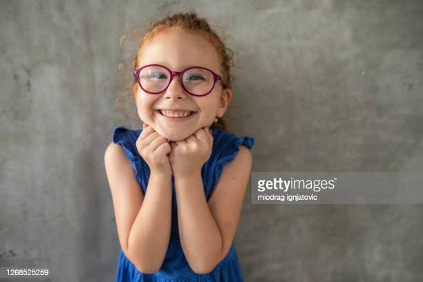 redhead cross-eyed girl standing in front of gray wall at home - hand on chin stock pictures, royalty-free photos & images