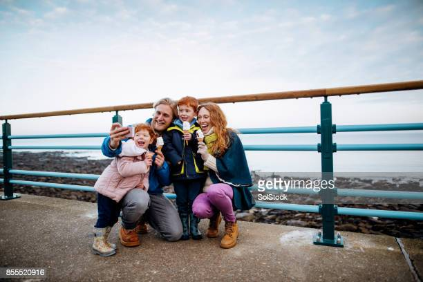 redhead family taking a selfie at the coast - coastline stock photos and pictures