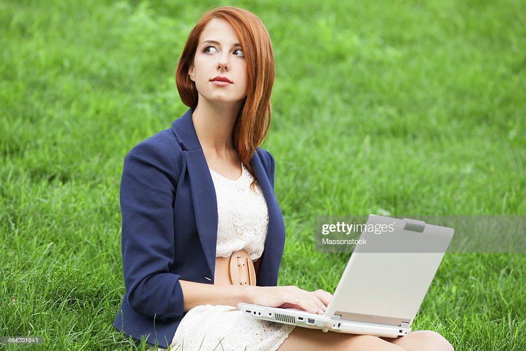 Pelirrojo girl at green grass con portátil : Foto de stock