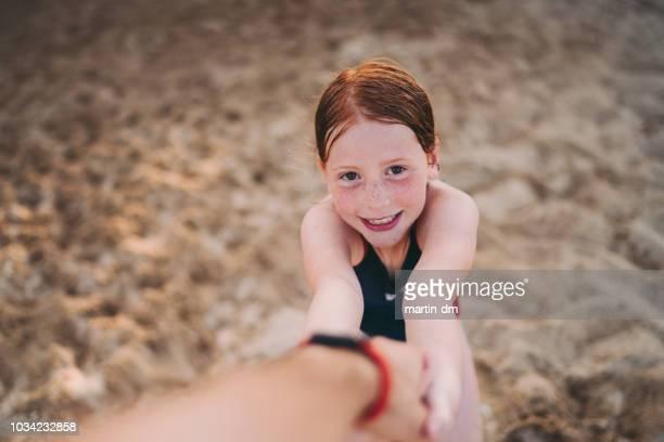 redhead ragazza in spiaggia vuole giocare con suo padre - soggettiva foto e immagini stock