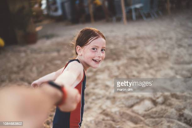 redhead girl at the beach wants to play with his father - attitude stock pictures, royalty-free photos & images