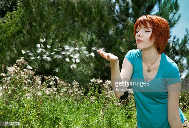 Redhead Girl Blowing Fuzzy Flower Seeds In Spring Air, Breeze