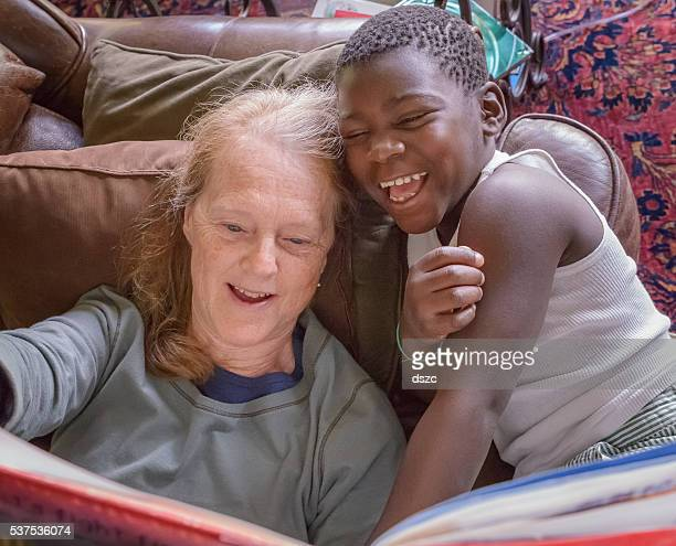 Redhead Grandmother Reading Story Book, Black Adopted Grandson, multiracial family